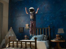 Imagem do filme Extraordinário (ou Wonder). Na imagem, Auggie usa um capacete de astronauta e pula em cima da cama. Na parede do quarto é desenhado um céu estrelado.