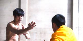 Imagem de A Origem do Dragão mostra Bruce Lee em pose de combate contra um inimigo de quimono amarelo.