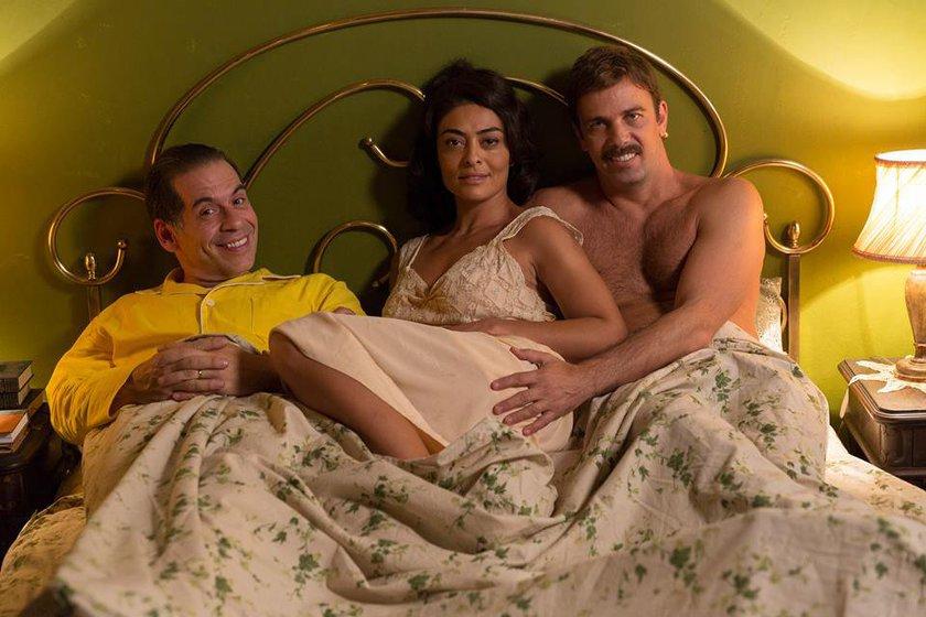 Imagem de Dona Flor e Seus Dois Maridos mostra flor na cama com Vadinho à direita e Teodoro à esquerda
