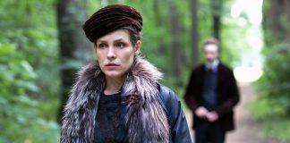 Imagem de Lou mostra a personagem-título usando um casaco de pele e uma boina enquanto se afasta de uma figura desfocada em uma área florestal