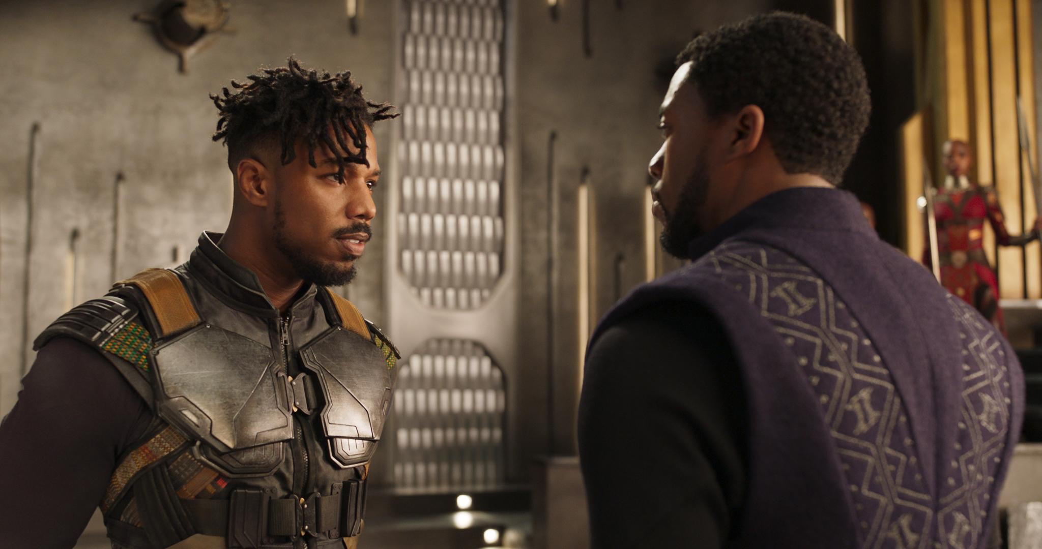 A Imagem mostra o protagonista de Pantera Negra, T'Challa, vivido por Chadwick Boseman à direita. À esquerda, o antagonista Erik, vivido por Michael B. Jordan. A imagem está em plano americano, da cintura para cima dos atores. Os dois se encaram de forma ameaçadora.