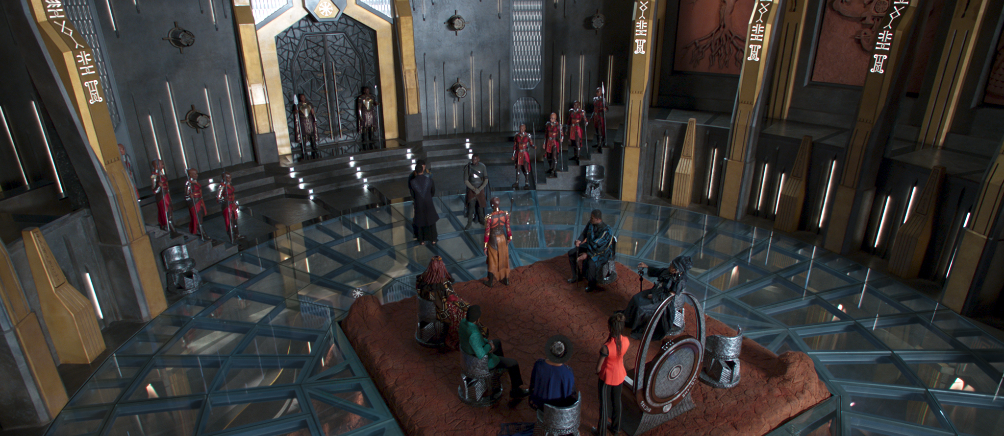 A imagem mostra a sala do trono de Wakanda, vista de cima e por trás. O trono está no canto inferior direito da imagem e os cinco representantes das tribos leais à coroa estão sentados ao seu redor, formando um semi círculo. À esquerda do trono, Shuri, a irmã de T'Challa, vivida por Letitia Wright. A frente do trono, A guarda Okoye, vivida por Danai Gurira. À frente de Okoye estão o rei T'Challa, vivido por Chadwick Boseman e Erik, vivido por Michael B. Jordan