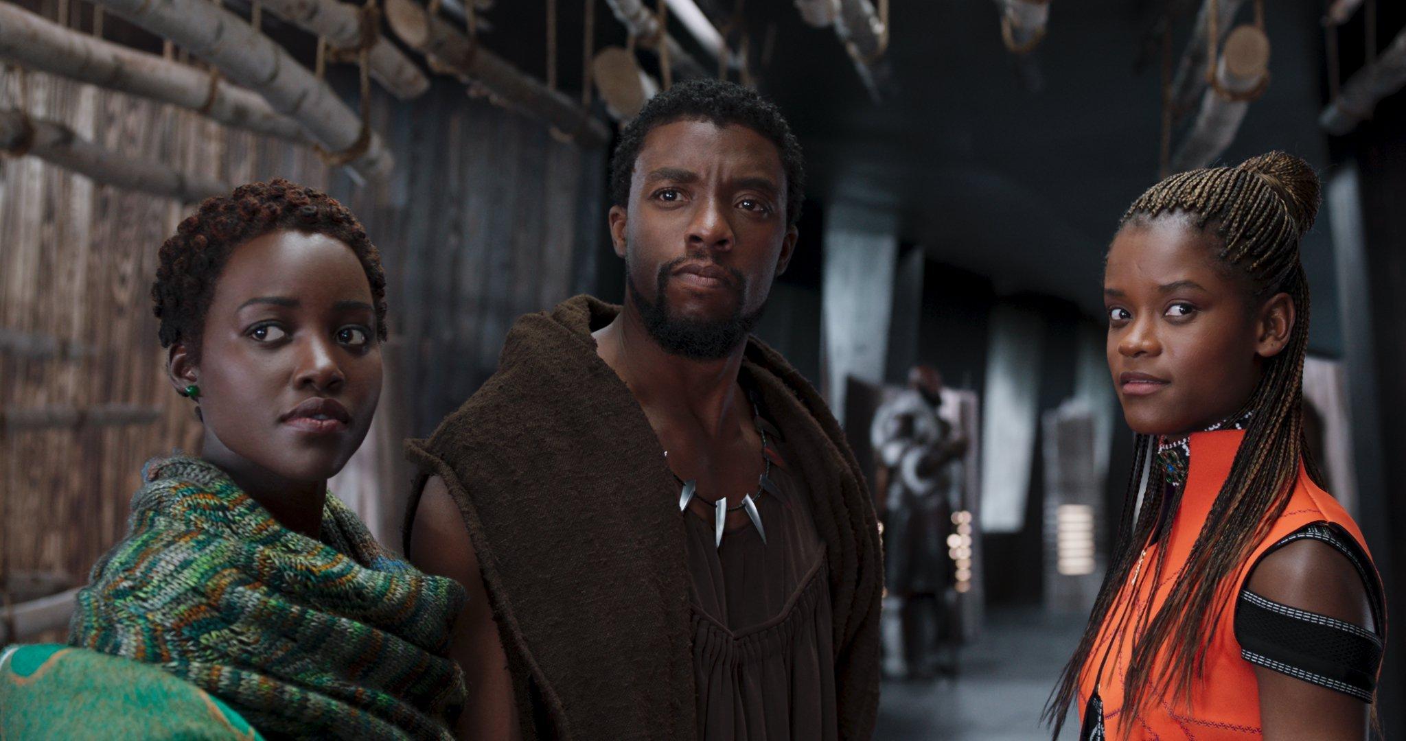 Em plano americano, da cintura para cima, a imagem mostra à esquerda, Lupita Nyong'o, como Nakia, ao centro Chadwick Boseman como T'Challa e à direita Letitia Wright como Shuri, personagens do filme Pantera Negra, da Marvel Studios.